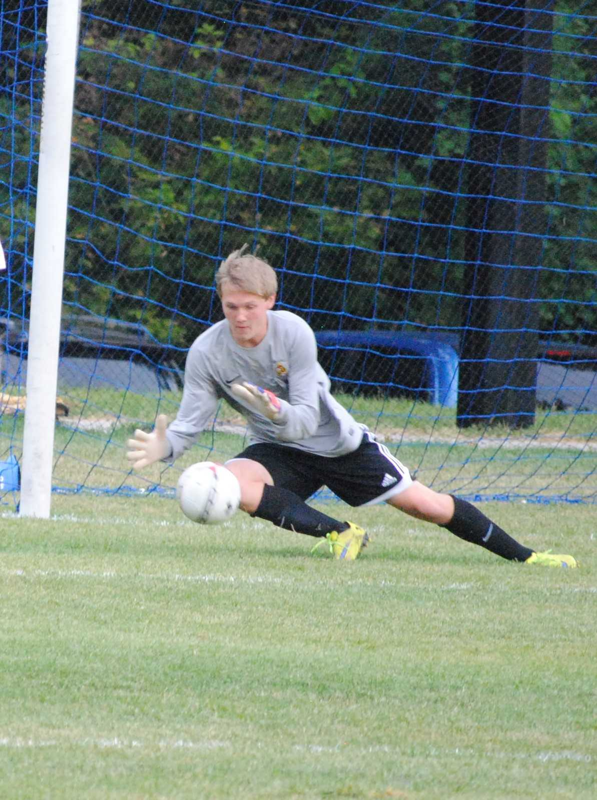 Senior Tyler Brown dives for a save during a 2015 varsity boys soccer game. Brown has suffered seven concussions and has had to stop playing soccer as a result.