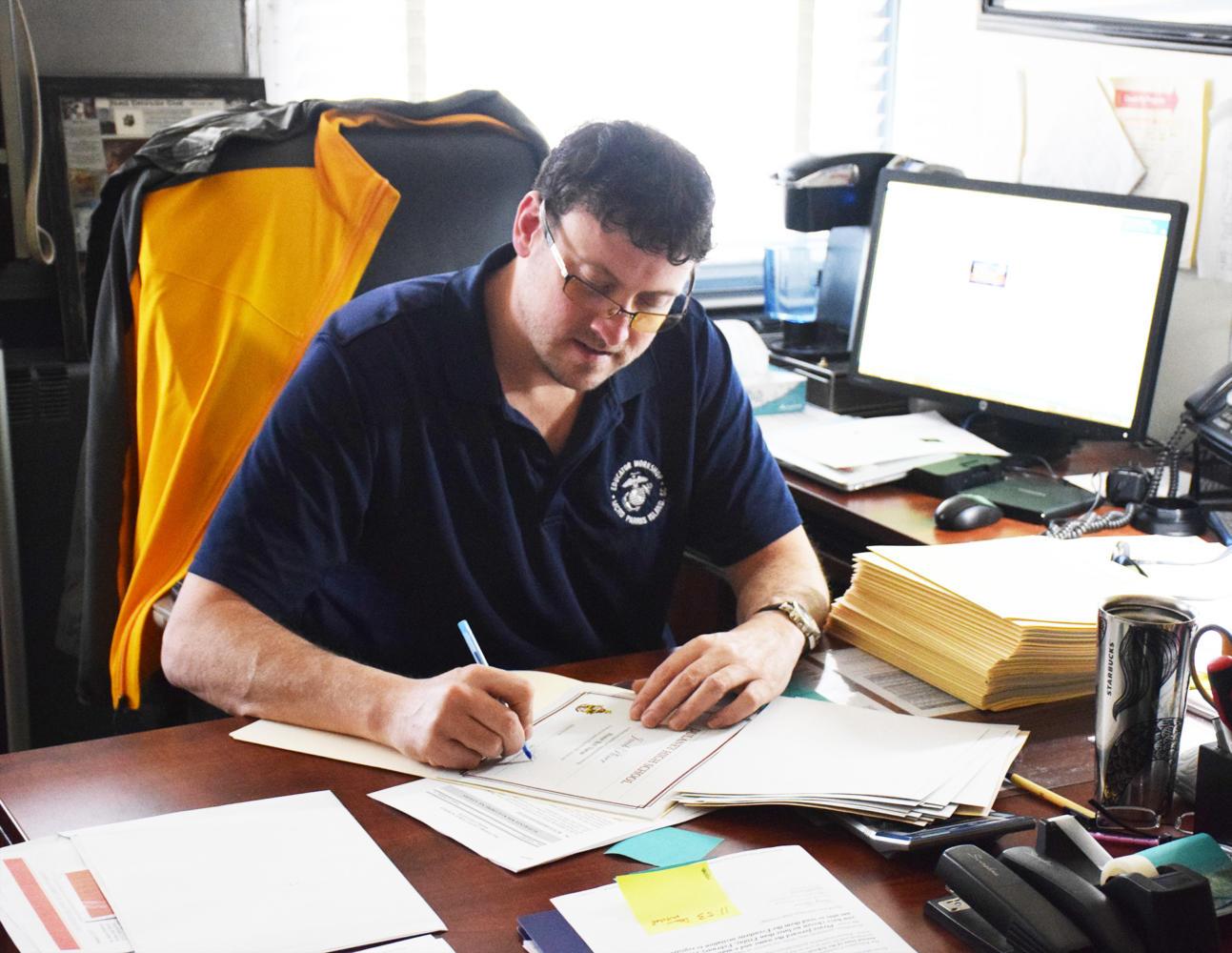 Principal Sam Wynkoop signs Honor Roll certificates in his office Feb. 9.