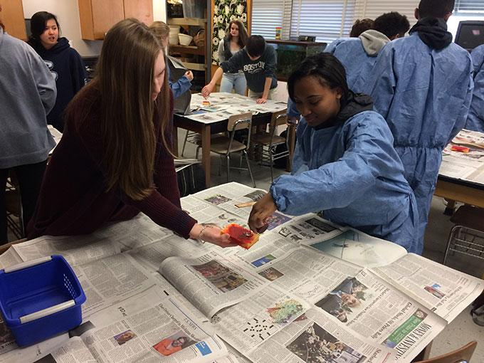 """(Left to Right) Seniors Sara DeFelice and Arianna Graham hit a bamboo sponge packed with fake blood on March 21 during Marci Phillips' A1 Honors Forensics class. The activity was done to observe blood spatter patterns on vertical and flat surfaces to create a model crime scene. """"It was fun because we got to put our anger out on the sponge, and we got to make it look really bloody everywhere,"""" Graham said."""
