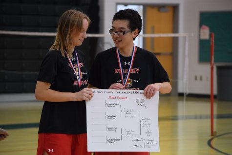 (From left to right) Freshman Nicolette Samek and senior Ari Wu pose with the Mixed Double scoreboard after winning gold in the tournament Oct. 29 at George Washington Carver Center for Arts and Technology.