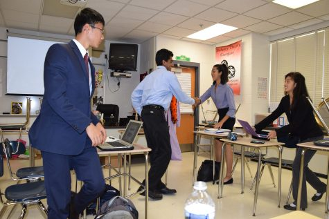 (From left to right) Students from River Hill High School shake hands with a sophomore Olivia Summons and senior Jessica Ye after the debate about the benefits and costs of the Internet of Things