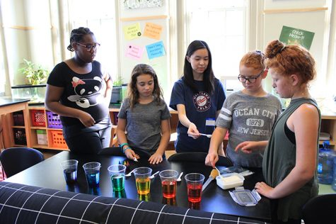 Senior Allie Ng (center) makes sugar rainbows by pouring sugar into multicolored glasses of water with middle school students at the Baltimore Montessori Public Charter School Oct. 17. The experiment demonstrated density by varying the amount of sugar in each glass.