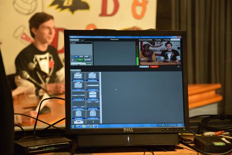 A monitor in the morning announcements room shows the new program, NewTek Tricaster, on screen. The program allows student broadcasters to view anchors as they deliver the morning announcements (see: senior Daniel Longest both behind the monitor and on the screen).