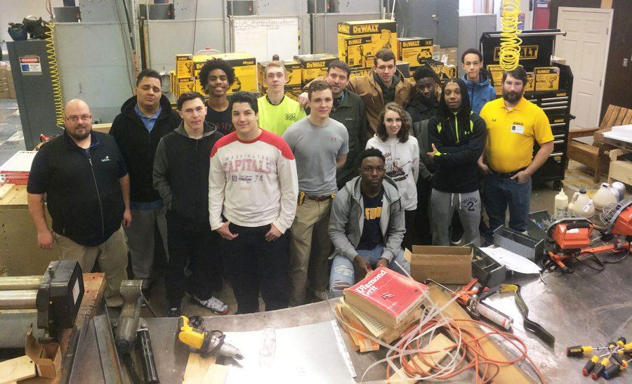 Technical ed. chairman Jamie Gaskin (left) and DeWALT Field Marketing Coordinator Anthony Harris (right) flank the period 1A HVAC 3 Honors class Feb. 17 following Harris's corporate donation of roughly $16,000 in tools. Principal Sam Wynkoop (center) joined the class for the announcement. The addition of the tools will allow students to work more efficiently since they will no longer need to wait for tools to recharge, Gaskin said. Harris said he read about the HVAC program in a newspaper and wanted to help prepare students for jobs in the field after high school.