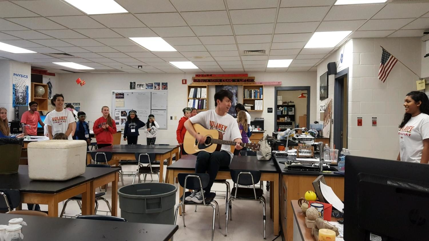 Senior Michael Cheng performs a song about DNA on his guitar for elementary school students in room 214.