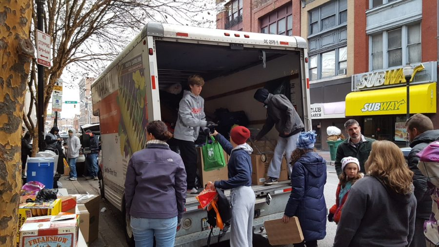 Sophomore Nick Leone, along with his family, hands out food and other neccessities to the homeless at the corner of Baltimore and Gay street Nov. 26.