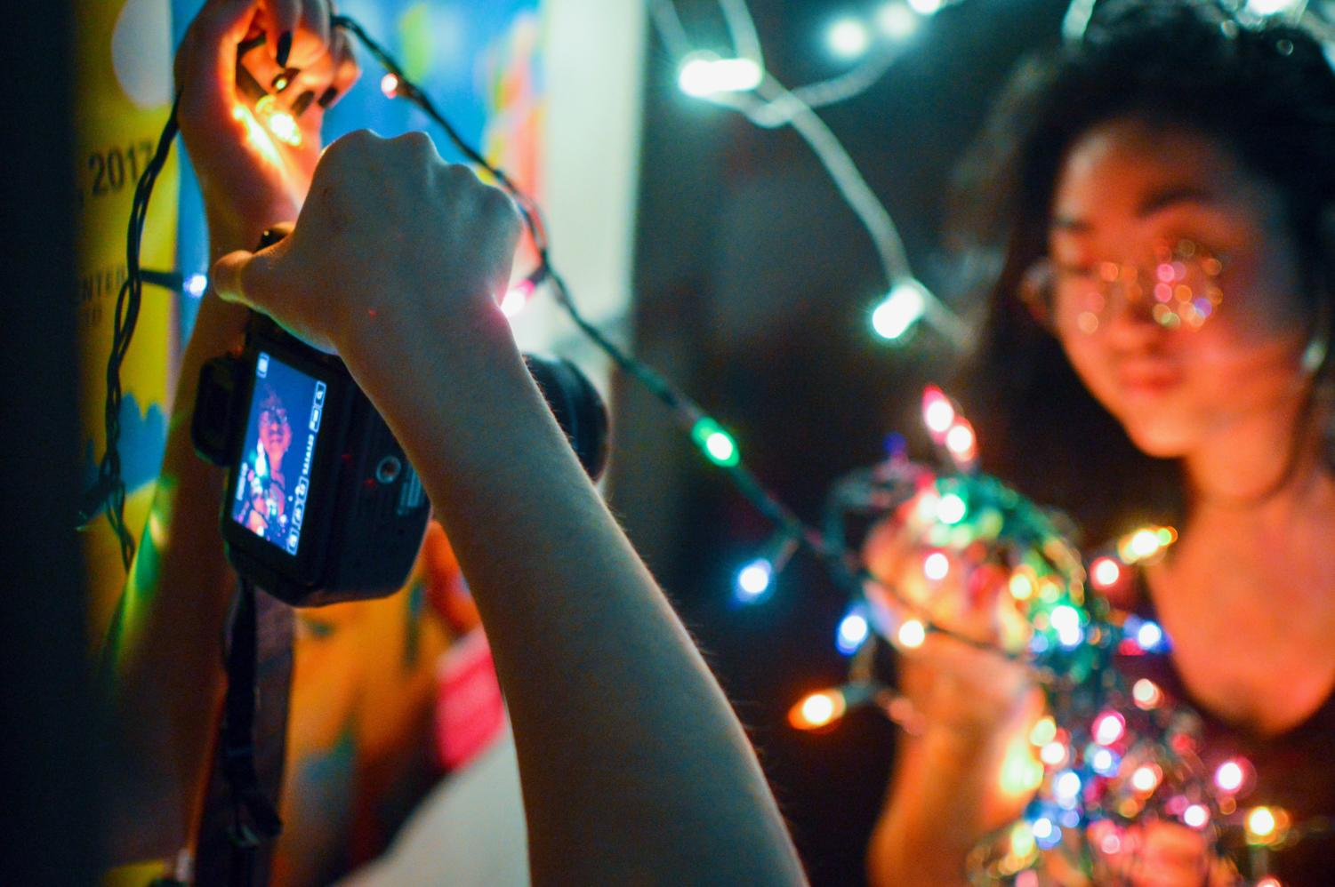 Junior Sasha Howard photographs junior Lucia Qian modeling for a string lights photoshoot.