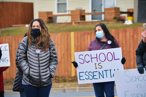two women stand, one holds sign reading 'school is essential'